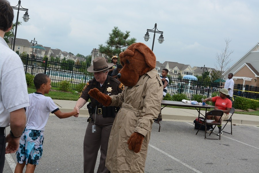 Master Cpl. Judith Thompson and McGruff the Crime Dog greet a youngster at a National Night Out neighborhood gathering.
