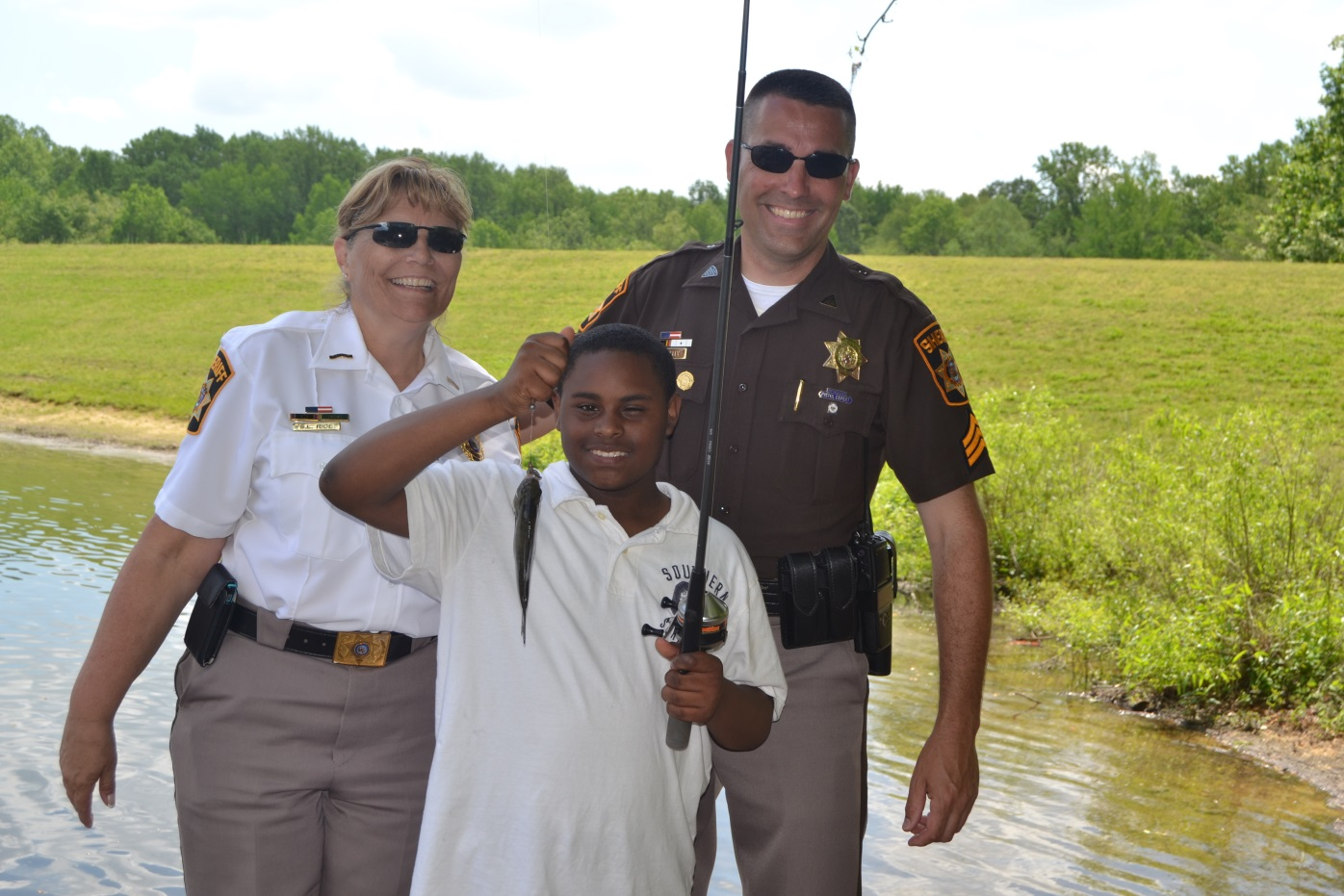 CCDC Director Susie Rice, Sgt. David Kelly, and a student pose with their catch